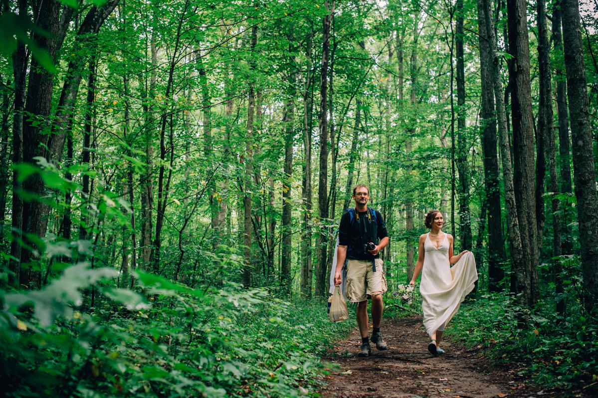bride groom walking through woods before elopement by best wv wedding photographers the oberports