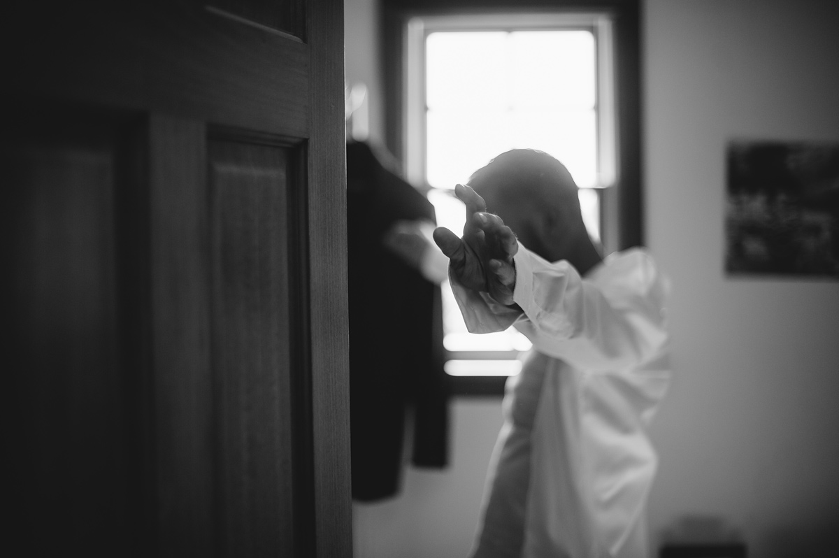 groom putting on shirt in black and white