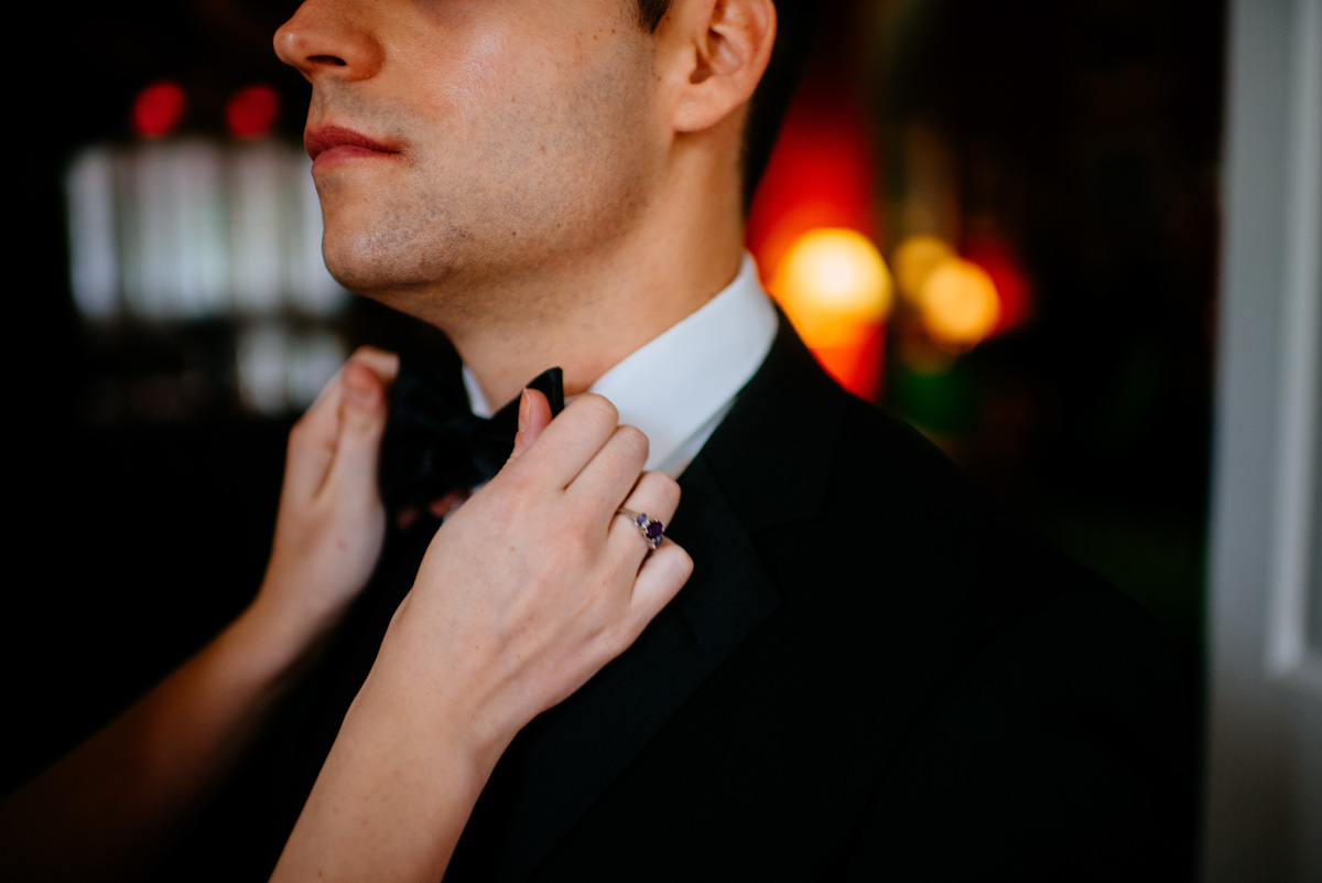 groom adjusting bow tie at the greenbrier