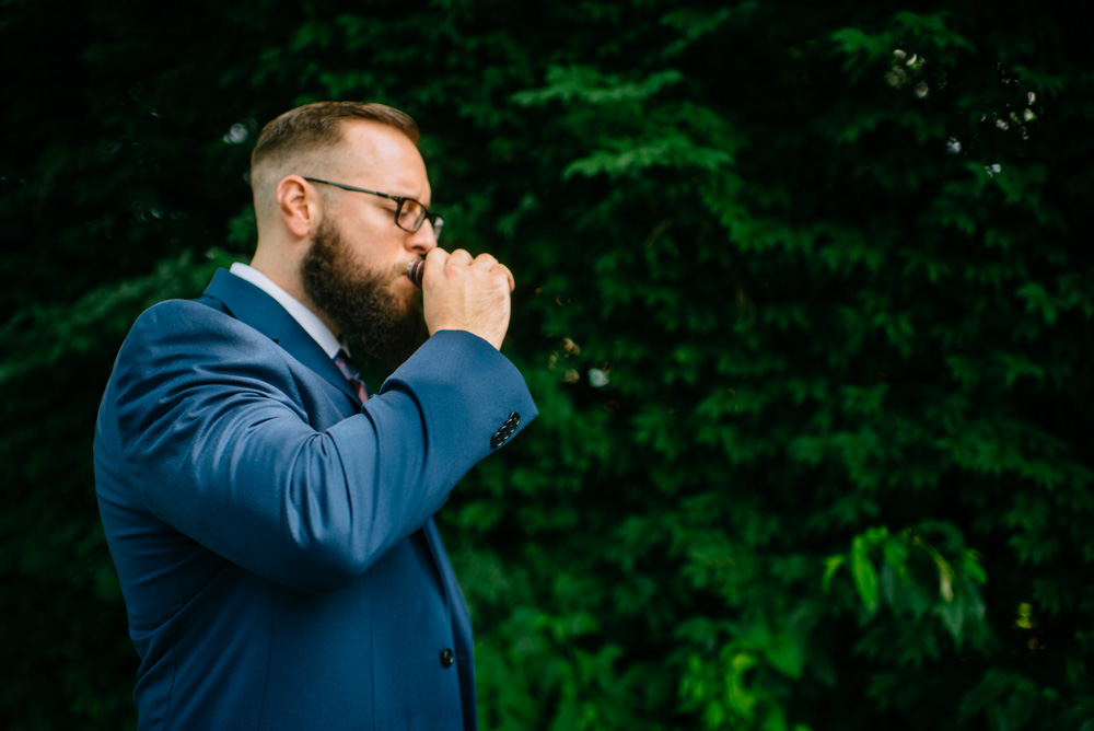 groom sips from a flask before first look