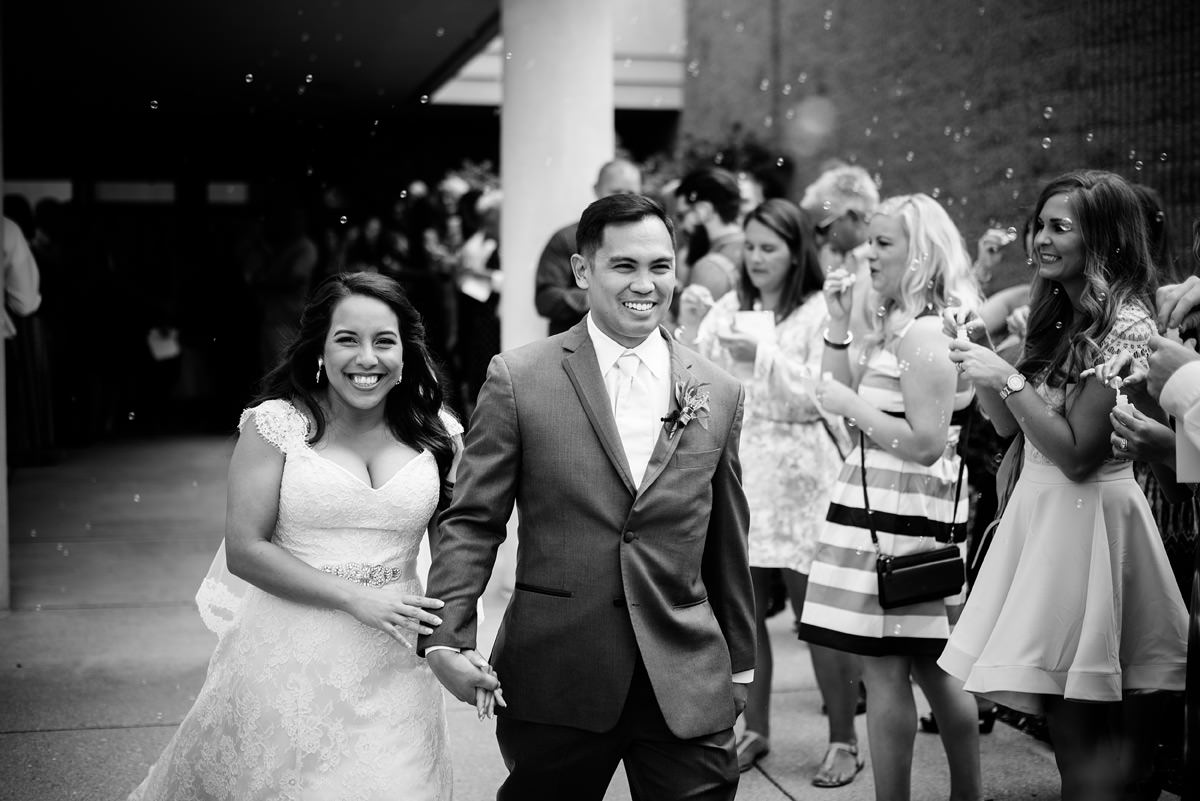 bride and groom exit church with bubbles
