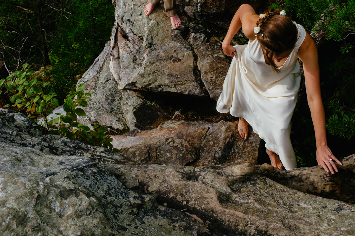 fayetteville bride climbing rocks on wedding day by theoberports