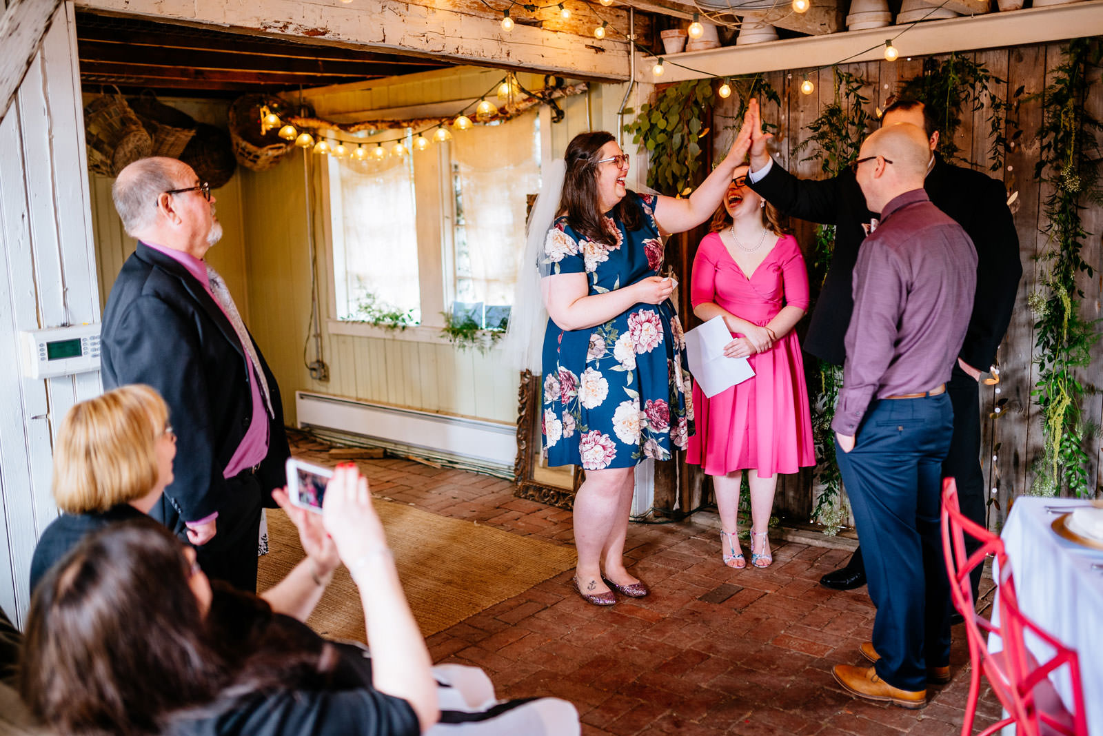 bride high fives officiant brother during ceremony in mushroom house terrain elopement