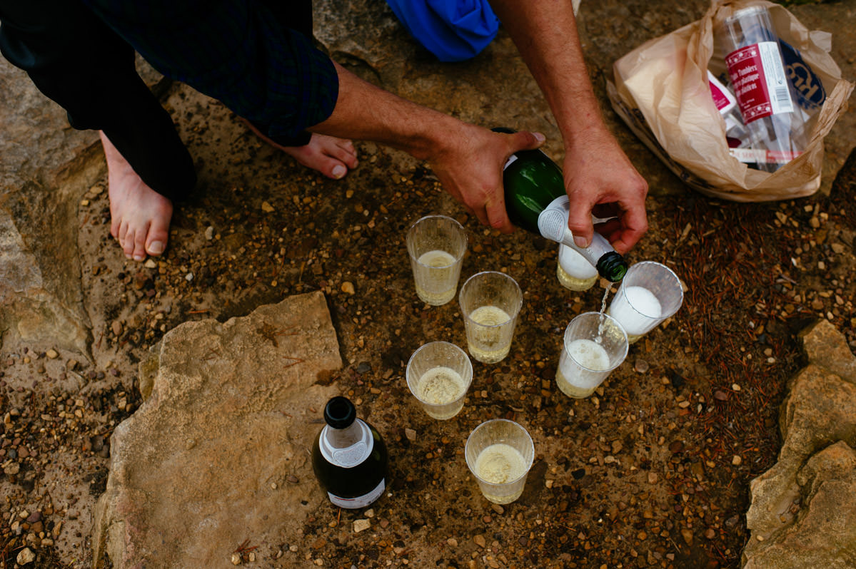 pouring champagne on long point trail after ceremony