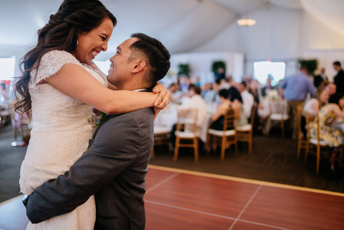 groom lifts bride up during first dance