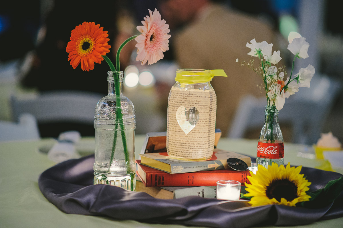 diy wedding table centerpiece detail with flowers bottles books