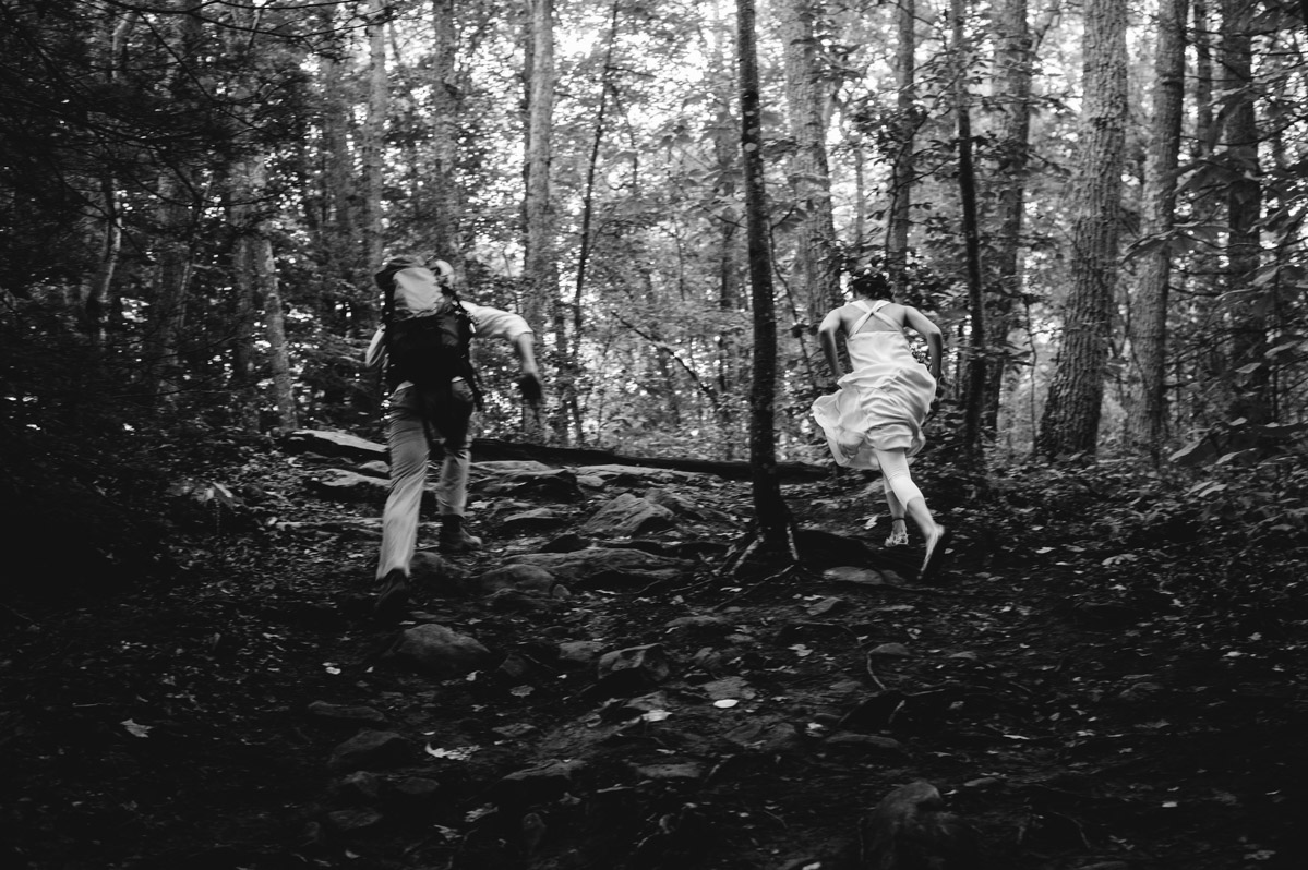 bride groom running through woods by best wv wedding photographers the oberports