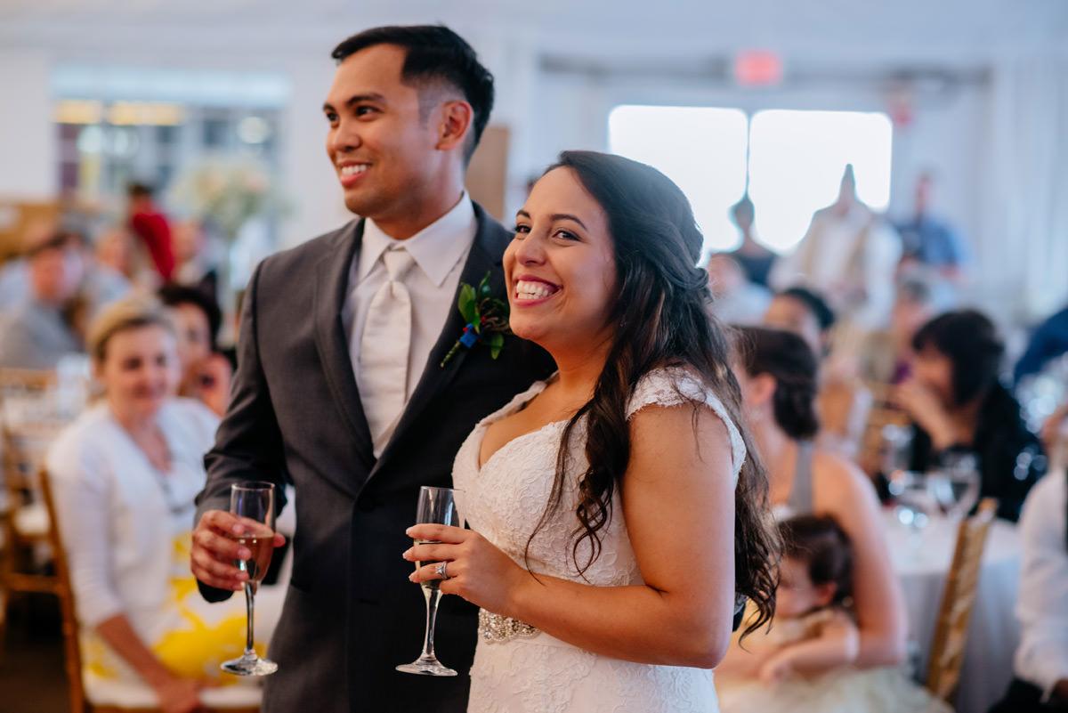 bride and groom enjoy speeches at wedding reception