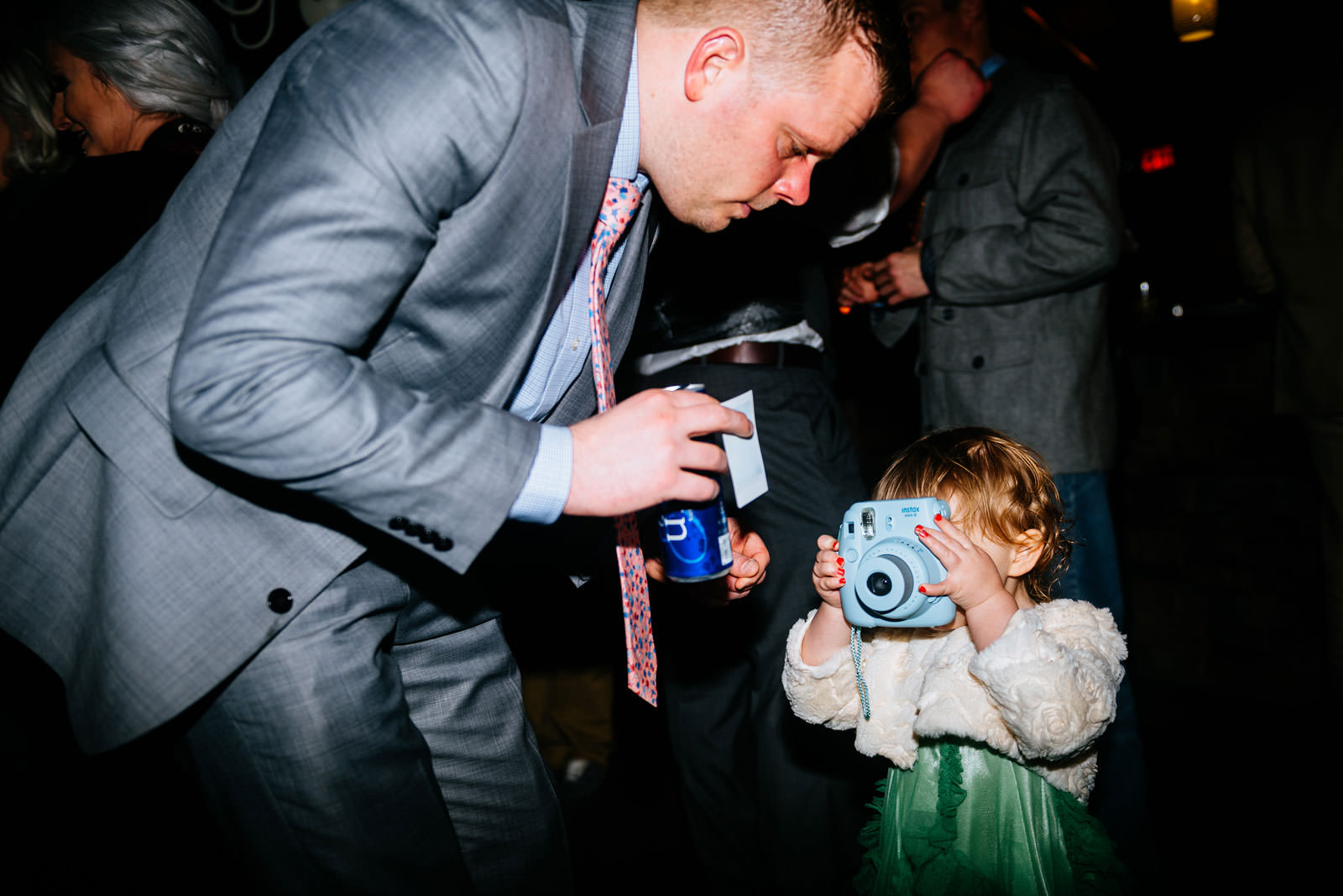 kid using instax camera at wedding reception
