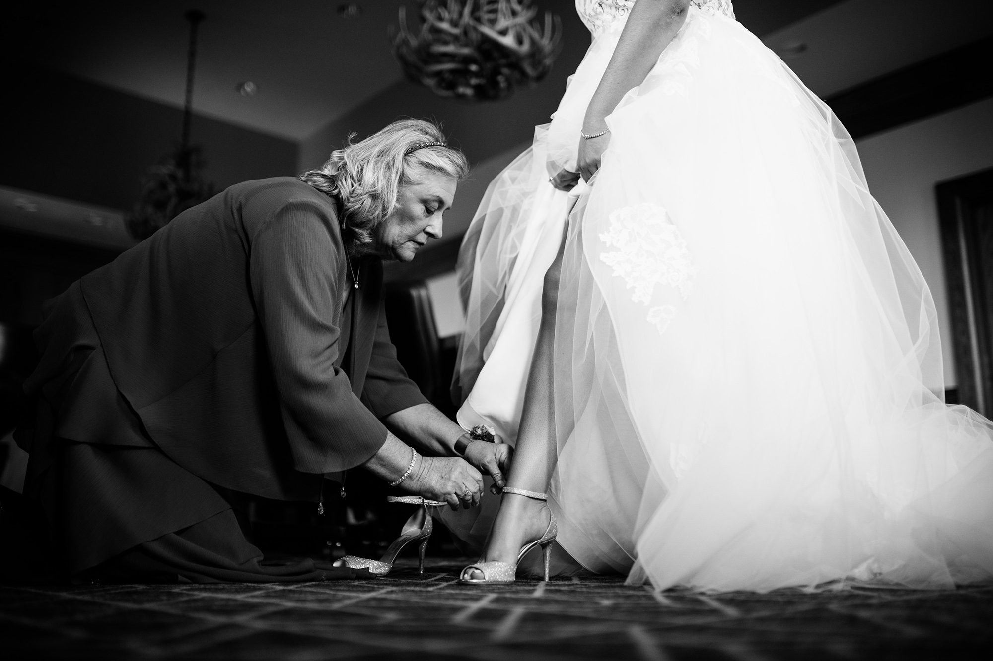 mom putting on brides shoes