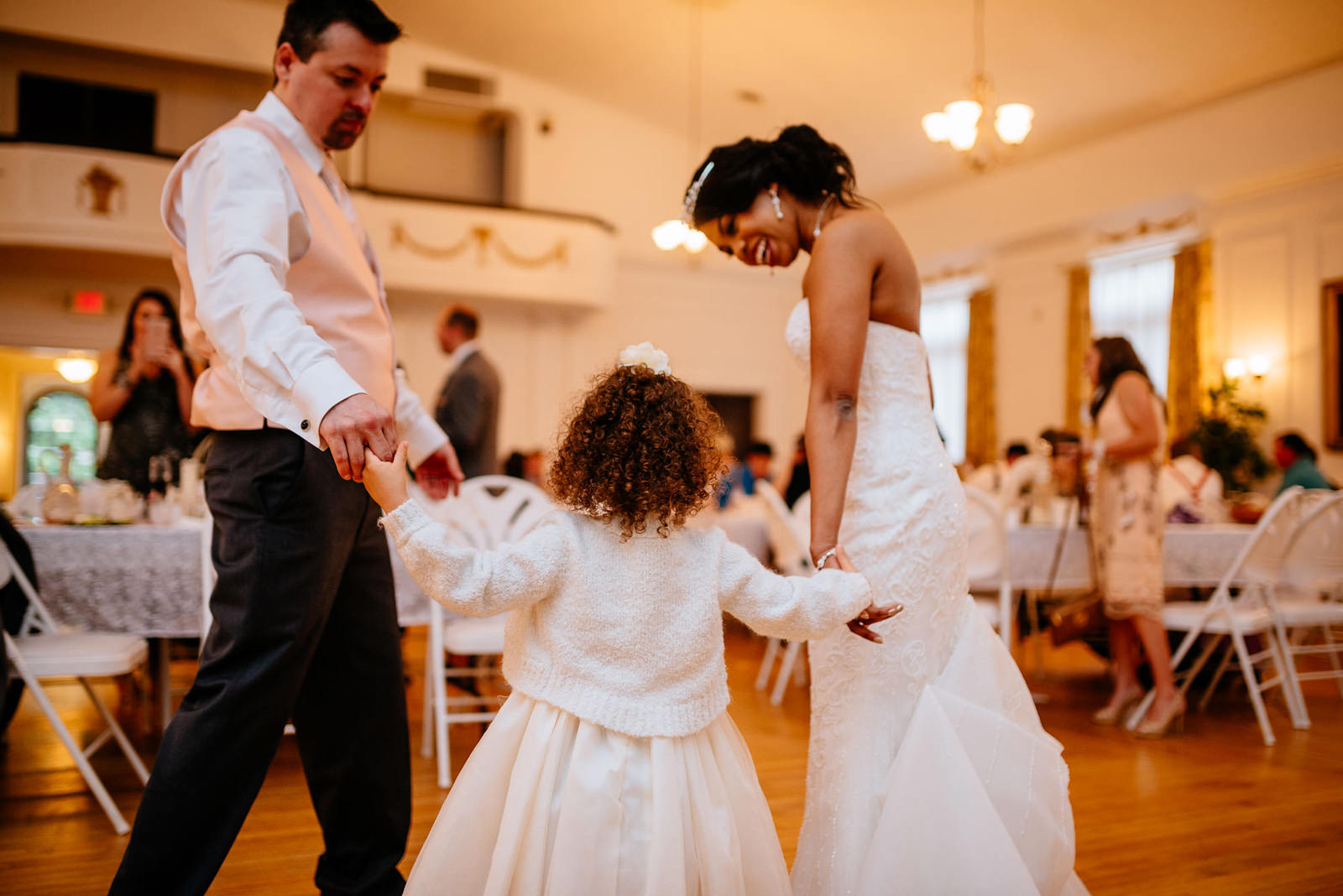 bride and groom dancing with flower girl